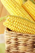 Crude corns in basket on napkin on wooden table
