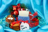 Cookies for Santa: Conceptual image of ginger cookies, milk and christmas decoration on blue backgro