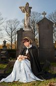 Widow in Victorian dress sitting on a tombstone
