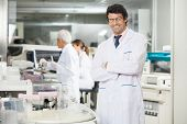 Portrait of smiling male researcher standing arms crossed in laboratory near centrifuge