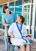 Happy female patient looking at friendly nurse while sitting on wheelchair at hospital courtyard
