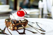 foto of brownie  - Chocolate and macadamia brownie with cherry on white dish - JPG