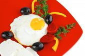 fried scrambled eggs eye with white goat feta cheese on red plate isolated over white background wit