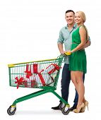 happiness, holidays, shopping and couple concept - smiling couple with shopping cart and gift boxes