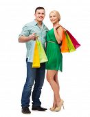 happiness, shopping and couple concept - smiling couple with shopping bags