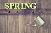 Watering can hanging in shed with the word Spring