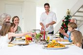 Happy multigeneration family enjoying Christmas meal at dining table