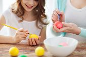 easter, family, holiday and child concept - close up of little girl and mother coloring eggs for eas