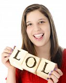A young teen laughing while holding rustic alphabet blocks with the letters LOL.  On a white backgro
