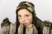 Close-up of an attractive young teen girl in camouflage looking over the top of an old wooden fence.
