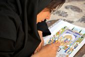 ESFAHAN, IRAN - DECEMBER 01, 2007: Muslim woman artist in black headscarf paints traditional Persian