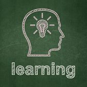 Education concept: Head With Lightbulb and Learning on chalkboard background