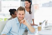 Handsome man smiling at camera while colleagues talk at desk in creative office