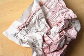 Tax forms crumpled up on wood surface