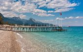 Small wooden pier on shingle beach and aquamarine water in popular touristic resort of Kemer on Medi