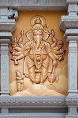 stock photo of vinayagar  - Hindu God Ganesh with Many Arms Carved Wall Relief on Exterior of Hindu Temple - JPG