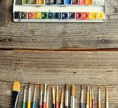 Professional watercolor aquarell paints in box with brushes on old wooden board