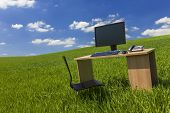 Business concept shot showing a computer on a desk in a green field with a blue sky and white clouds
