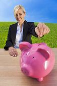 Investment concept shot of a beautiful young woman or businesswoman putting money coin into pink pig
