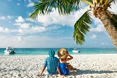 stock photo of couple sitting beach  - Couple in blue clothes on a tropical beach at Maldives - JPG