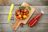 Cherry tomatoes on cutting board and ketchup bottle over wooden table background