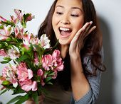Portrait of ecstatic woman with bunch of flowers looking at it surprisingly