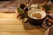 Mushroom soup in pot, on napkin,  on wooden background