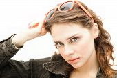 Beautiful Young Woman Puts On Sunglasses, Isolated On White
