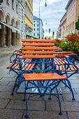 Attached cafe chairs on morning street