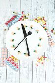 Medication schedule and meals. Conceptual photo. On wooden background