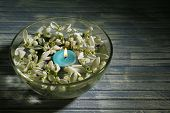 Beautiful snowdrops and candle in glass bowl with water, on wooden background