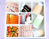 Medical pills, ampules in wooden box, on color background