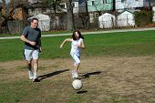 stock photo of father daughter  - Father and daughter having fun playing soccer - JPG
