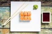 stock photo of chopsticks  - Seafood sushi rolls in white plate with chopsticks and japanese spices - JPG