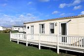 stock photo of trailer park  - Side view of modern caravan on trailer park with cloudscape background - JPG