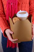 Woman holds box with coffee and cookies on grey background