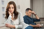 stock photo of conflict couple  - Sad Couple Sitting On Couch After Having Quarrel - JPG