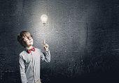 Genius boy in red glasses near blackboard with formulas