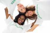 Team of happy volunteers embracing and looking down at camera on white background