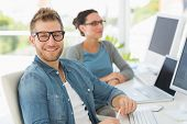 stock photo of keyboard  - Team of smiling designers with man looking at camera in creative office - JPG