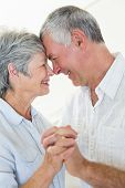 Happy senior couple dancing together head to head at home in living room