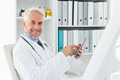 Portrait of a confident smiling male doctor using digital tablet at medical office