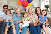 Portrait of multigeneration family celebrating girls birthday in living room