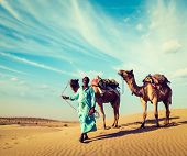 Vintage retro hipster style travel image of Rajasthan travel background - Indian cameleer (camel dri
