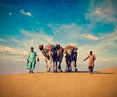 Vintage retro hipster style travel image Rajasthan travel background - two Indian cameleers (camel d