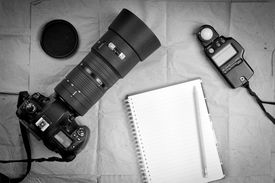 stock photo of grayscale  - Photography equipment including a professional digital SLR camera and light meter with a blank notebook - JPG