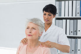 picture of chiropractor  - Female chiropractor massaging a senior womans shoulder in the medical office - JPG