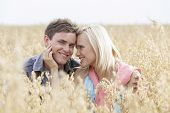 Portrait of happy man sitting with romantic woman amidst field