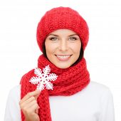 happiness, winter holidays, christmas and people concept - smiling young woman in red hat, scarf and mittens holding snowflake decoration over white background