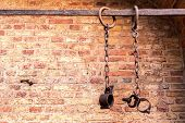 stock photo of torture  - Middle aged prisoners chains and cuffs over a brick wall